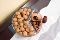 Walnuts and hazelnuts. On table in glass utensil Stock Photos