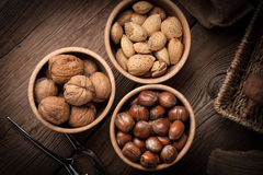 Walnuts, hazelnuts and almonds in-shell in wooden bowl. Stock Images