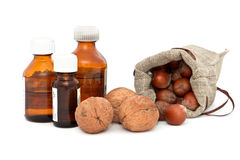 Walnuts, hazelnuts and bottles with different oils. Stock Photo