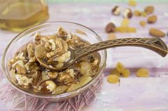 Walnuts, hazelnuts and honey in a glass dish Royalty Free Stock Photo