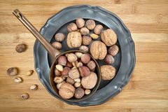 Nuts of various kinds on a metal plate, centrally from above on a wooden board. Walnuts, hazelnuts and pistachios - various kinds of nuts on a metal plate. from stock photo