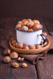 Walnuts, hazelnuts. In a white cup on a dark background stock photo