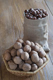 Walnuts and hazelnuts on a wooden table. Walnuts in a wicker basket and hazelnuts in a cotton bag on a wooden table Stock Photography