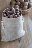 Walnuts and hazelnuts on a wooden table. Walnuts in a wicker basket and hazelnuts in a cotton bag on a wooden table Royalty Free Stock Photo