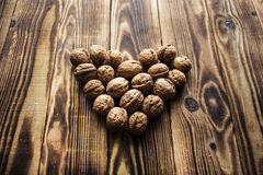 Walnuts in heart on wooden background Stock Photo