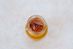 Walnuts in honey jar Stock Images