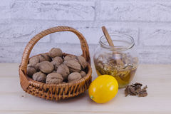 Walnuts in a jar of honey and a lemon Royalty Free Stock Image