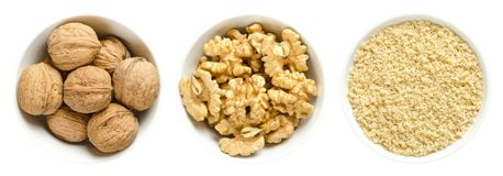 Walnuts, kernel halves and ground walnuts in white bowls stock photo