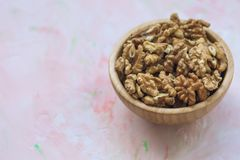Walnuts kernels, peeled nuts in a wooden bowl on a pink background. Concept of healthy eating vegan food Close up, selective focus, copy space stock images