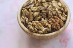 Walnuts kernels, peeled nuts in a wooden bowl on a pink background. Concept of healthy eating vegan food Close up, selective focus, copy space stock photography