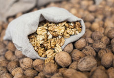 Walnuts kernels in the sack on the pile of walnuts Royalty Free Stock Images