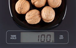 Walnuts on kitchen scale Royalty Free Stock Photography