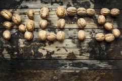 Walnuts, laid out in the word nuts on wooden rustic background, top view Royalty Free Stock Photography