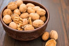 Walnuts lie in a bowl, next to them are chopped nuts on a wooden floor.  royalty free stock images