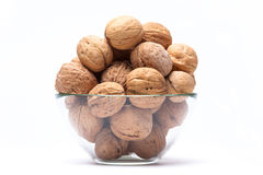 Walnuts lie in a glass bowl isolated on white royalty free stock image