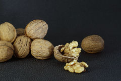Walnuts lie in a heap on a dark background, one is split, half the shell and a delicious kernel. Stock Photo