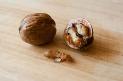 Walnuts lie on a wooden surface Royalty Free Stock Image