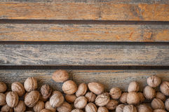 Walnuts. Many walnuts in a vintage wooden background. Autumn composition Stock Photography