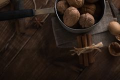 Walnuts in a metal bowl, dark background. Walnut shell and cinnamon on the wooden table. Top view Royalty Free Stock Image