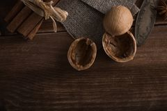 Walnuts in a metal bowl, dark background. Walnut shell and cinnamon on the wooden table. Walnut shell and cinnamon on the dark wooden table Royalty Free Stock Image
