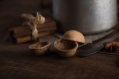 Walnuts in a metal bowl, dark background. Walnut shell and cinnamon on the wooden table. Walnut shell and cinnamon on the dark wooden table Stock Photos