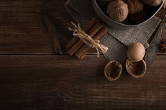 Walnuts in a metal bowl, dark background. Walnut shell and cinnamon on the wooden table. Royalty Free Stock Images