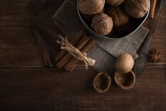 Walnuts in a metal bowl, dark background. Walnut shell and cinnamon on the wooden table. Royalty Free Stock Photography