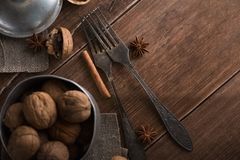Walnuts in a metal bowl, dark background. Walnut shell and cinnamon on the wooden table. Royalty Free Stock Photo