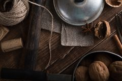 Walnuts in a metal bowl, dark background. Walnut shell and cinnamon on the wooden table. Top view Stock Photography