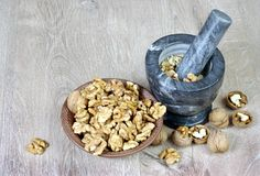 Walnuts in a mortar with pestle. crushed nuts. Food rich in proteins stock photos