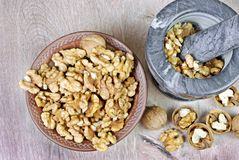 Walnuts in a mortar with pestle. crushed nuts. Top view stock image