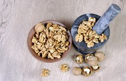 Walnuts in a mortar with pestle. crushed nuts. Top view stock photography