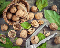 Walnuts, nutcracker and basket on old table, top view. Royalty Free Stock Photos