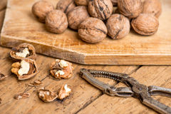 Walnuts and nutcracker on an old wooden rustic table Royalty Free Stock Photo