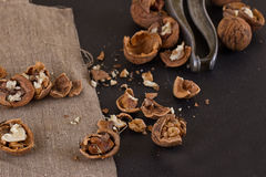Walnuts and nutcracker on table covered with burlap Stock Images
