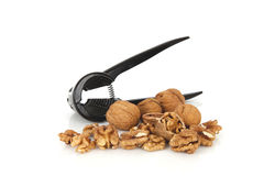 Walnuts with a nutcracker on a white background Stock Photos