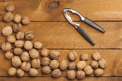 Walnuts and nutcracker on wood Royalty Free Stock Image