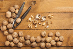 Walnuts and nutcracker on wood Royalty Free Stock Photography