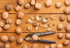 Walnuts and nutcracker on wood Stock Photos