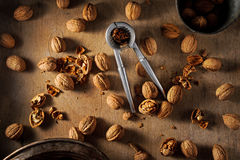 Walnuts and nutcrackers  on a wooden background Stock Photos