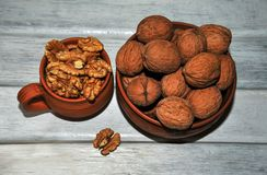 Walnuts, nuts in pottery, peeled and unpeeled on a white table. royalty free stock photos