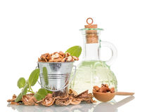 Walnuts oil and nuts. In wooden bucket and spoon on white background royalty free stock photo