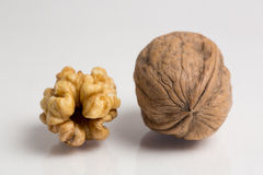 Walnuts. One shelled and one unshelled organic walnut on white background, closeup view Royalty Free Stock Photo