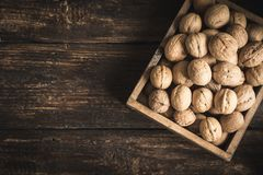 Walnuts. Organic Walnuts in rustic wooden box, top view, copy space. Seasonal harvest of walnuts royalty free stock image