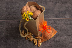 Walnuts in a paper bag and a small bouquet of wild flowers on a dark background Royalty Free Stock Images