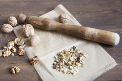 Walnuts in paper and wood battledore on a wooden background Stock Photos