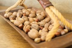 Walnuts and peanuts in wooden bowl with handle royalty free stock photography