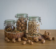 Walnuts,Peeled walnuts,pistachios,Brazil nuts in glass jar on wooden stand Royalty Free Stock Photo