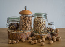 Walnuts,Peeled walnuts,pistachios,Brazil nuts in glass jar on wooden stand. Nuts in glass jar on wooden stand bamboo table Royalty Free Stock Image
