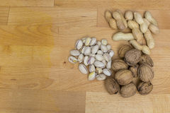 Walnuts, pistachios and peanuts on a wooden background Stock Photography